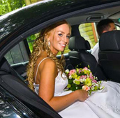 lady in wedding dress sitting in a limo